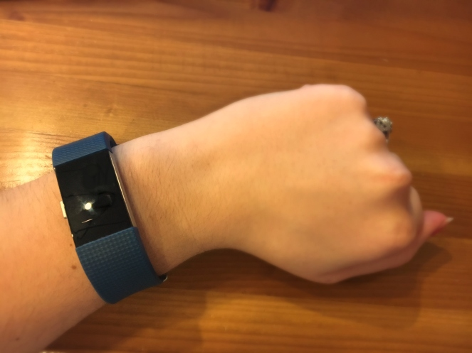 Fitbit on wrist with wood background