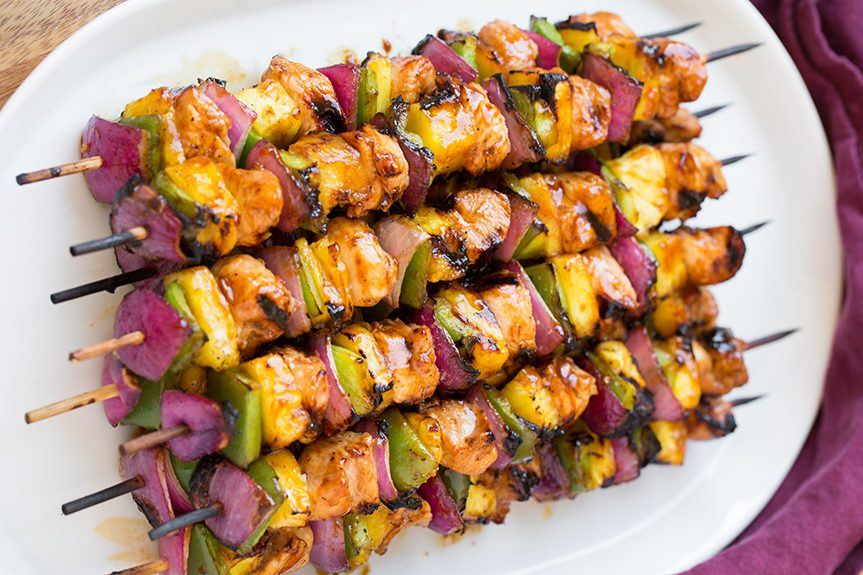 long hawaiian chicken kebabs on plate